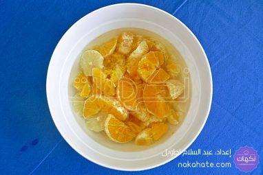قطع البرتقال والقشرة المبشورة مع الماء