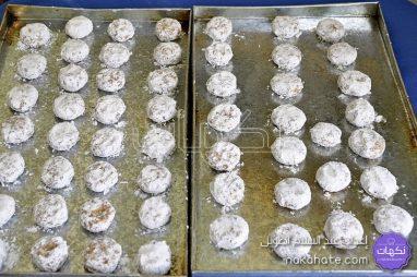 تفنيد كويرات حلوى الغريبة في السكر الناعم ووضعها في صفيحة الفرن
